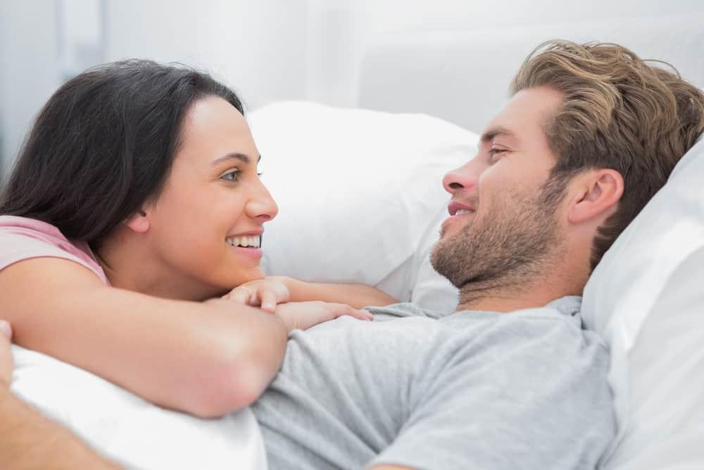 Ein Mann mit Bart und seine Frau unterhalten sich im Bett