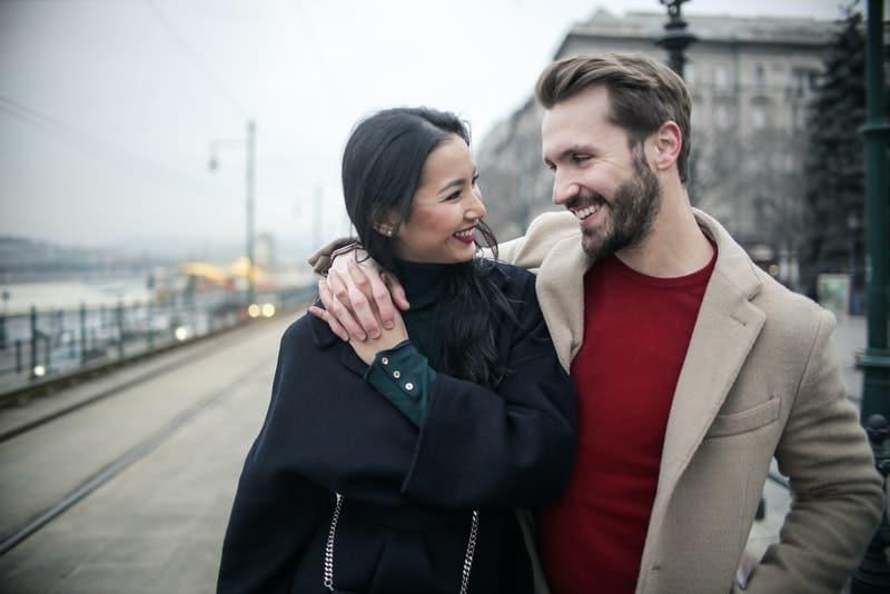 Ein Mann mit Bart und seine asiatische Frau gehen umarmend herum
