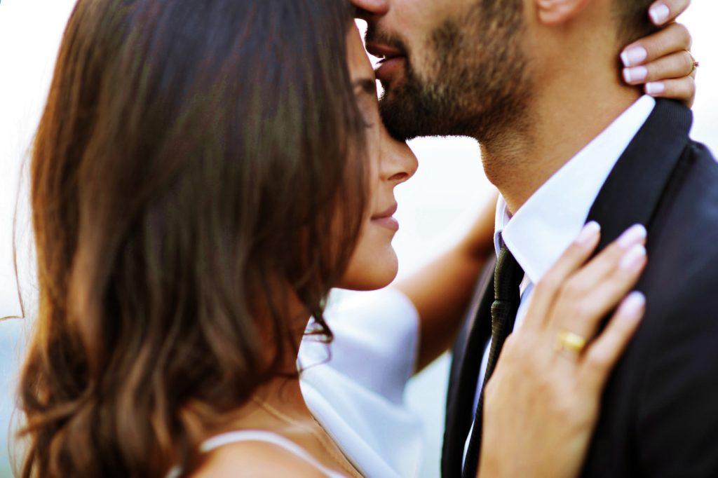 Ein Mann mit einem Bart in den Armen einer Frau küsst sie auf die Stirn