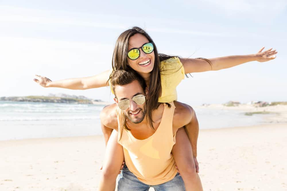Ein Mann trägt eine Frau zum Strand und sie lachen