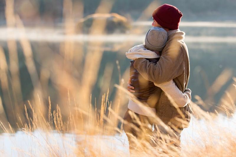 Ein Mann umarmt ein Mädchen im Gras