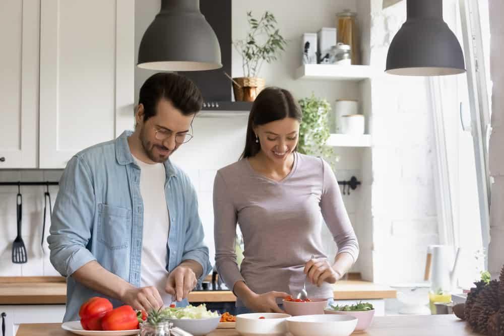 Ein Mann und eine Frau bereiten das Mittagessen in der Küche vor