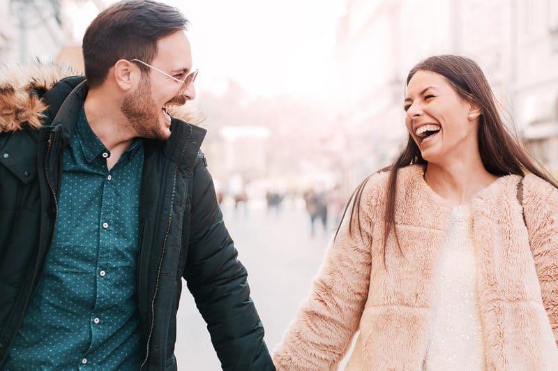 Ein Mann und eine Frau halten Hände, lachen und gehen die Straße entlang