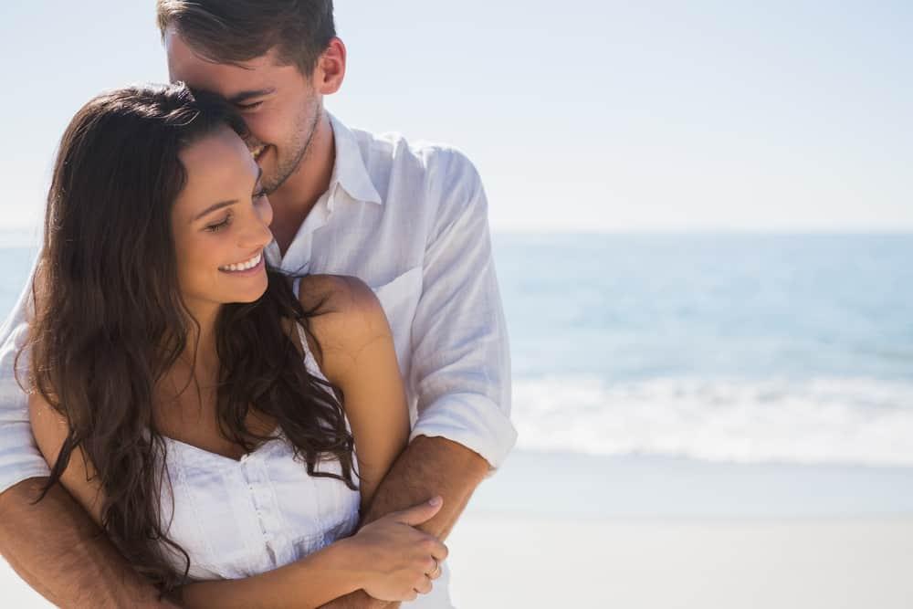 Ein Mann und eine Frau umarmen sich am Strand