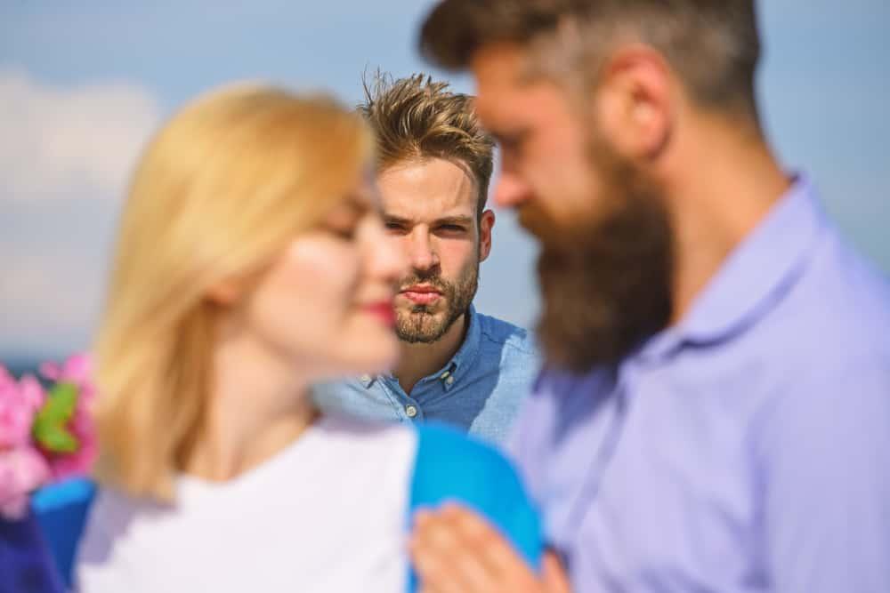 Ein eifersüchtiger Mann beobachtet das glückliche Paar