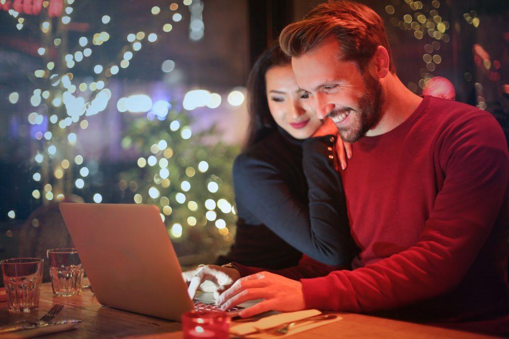 Ein lächelnder Mann und eine lächelnde Frau auf seiner Schulter arbeiten für einen Laptop