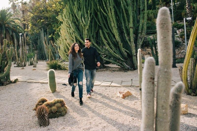 Ein lächelndes Mädchen mit Hut geht mit ihrem Mann zwischen den Kakteen spazieren
