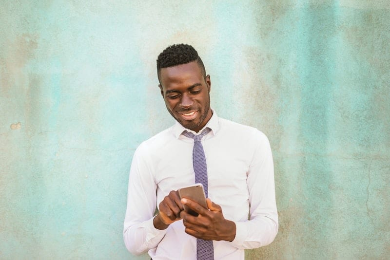 Ein schwarzer Mann in weißem Hemd und Krawatte benutzt ein Handy mit einem Lächeln
