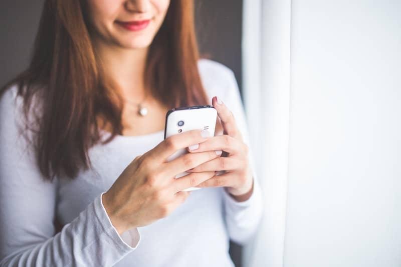 Eine Frau mit einem Lächeln schreibt eine SMS