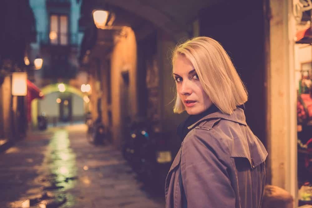 Eine ernsthafte Blondine geht die Straße entlang und schaut über ihre Schulter