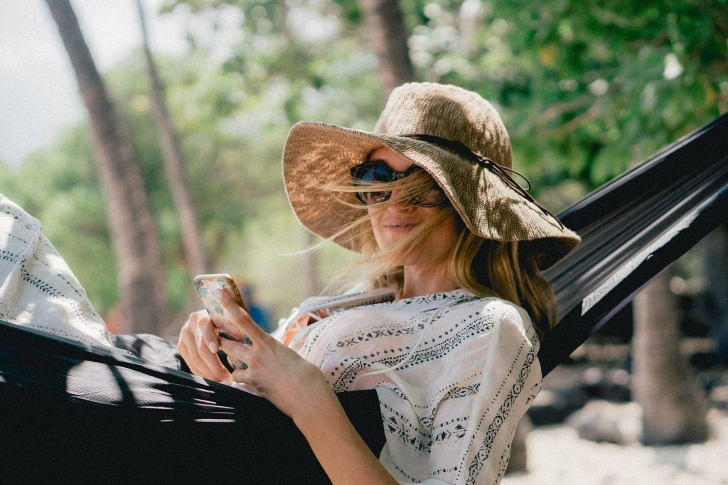 Eine lächelnde Frau ruht auf einer Schaukel und hält ein Handy in den Händen
