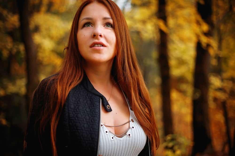 Eine rothaarige Frau steht stolz im Wald