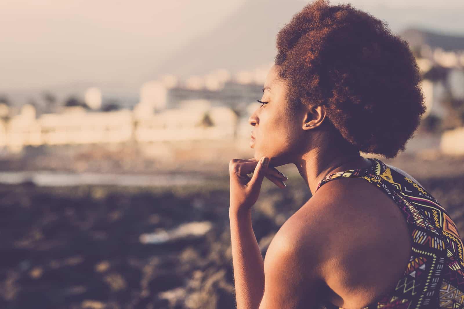 Eine schöne schwarze Frau denkt draußen