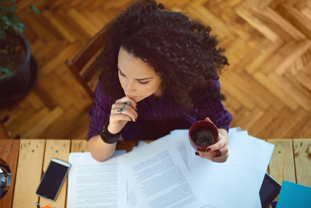 Eine schwarze Frau arbeitet zu Hause an ihrem Schreibtisch