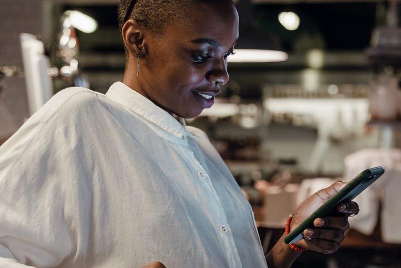 Eine schwarze Frau in einem weißen T-Shirt mit einem Lächeln im Gesicht liest eine SMS