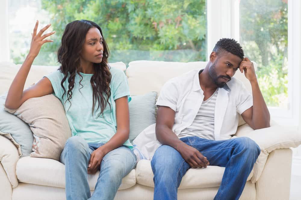 Eine schwarze Frau streitet mit ihrem schwarzen Mann auf der Couch