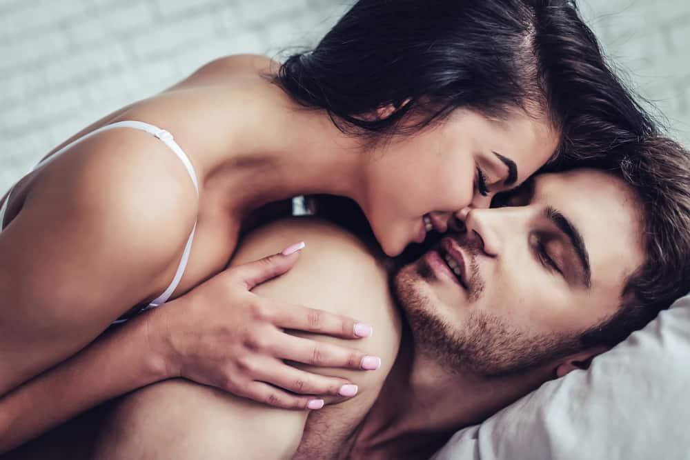 Eine schwarzhaarige Frau weckt ihren Mann mit Küssen