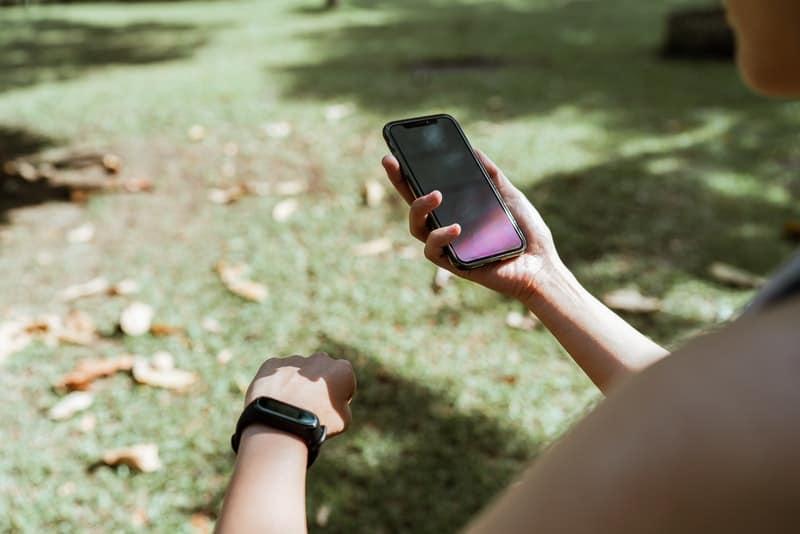 Frau, die im Park sitzt und Handy und Smartwatch betrachtet