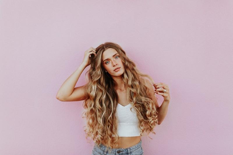 Frau, die neben rosa Wand steht, während sie ihren Kopf kratzt