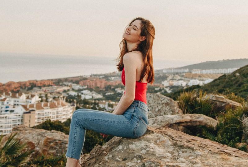 Frau, die tagsüber auf Felsen sitzt