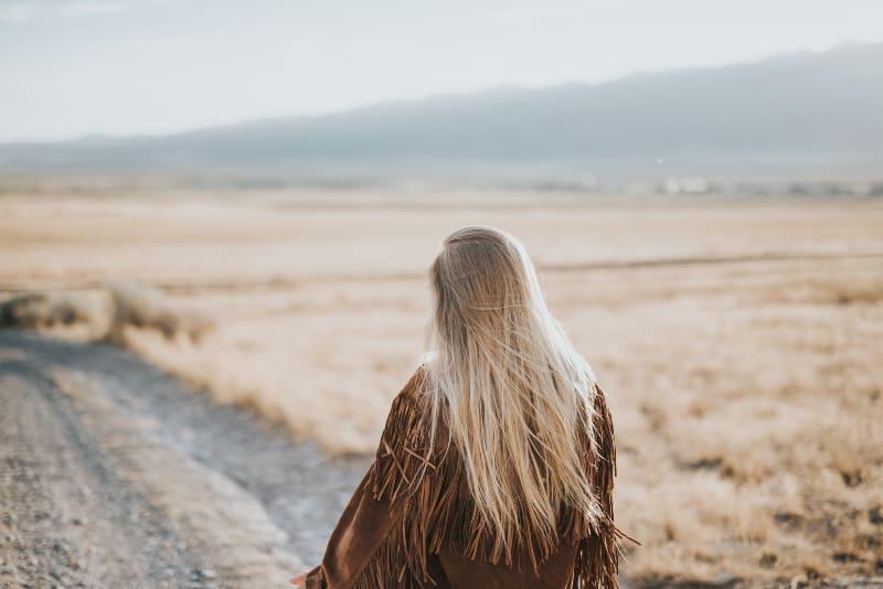 Frau geht auf grauem Sand
