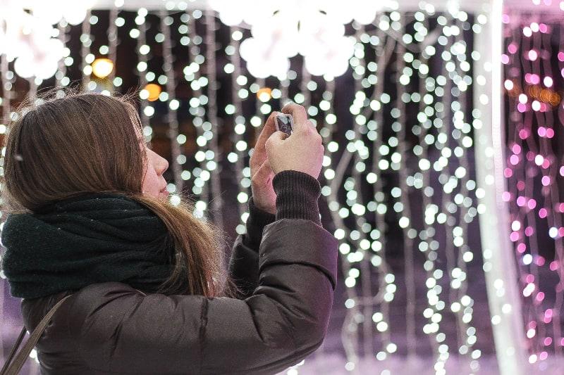Frau im schwarzen Schal mit Smartphone