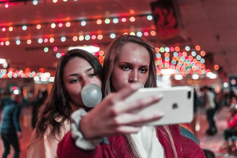 Frauen machen Foto im Gebäude in der Nähe von Menschen