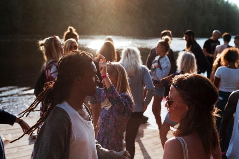 Gruppe von Menschen, die auf dem Dock neben dem Gewässer stehen