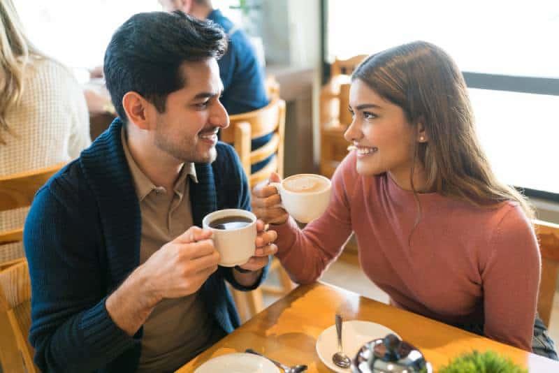 Junge Liebhaber genießen Kaffee, während sie sich in einem Café ansehen