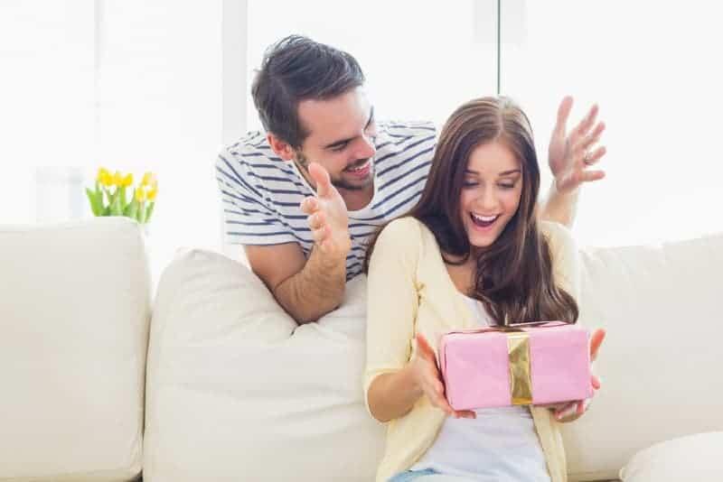 Mann, der ihrer Freundin zu Hause eine Geschenkbox gibt