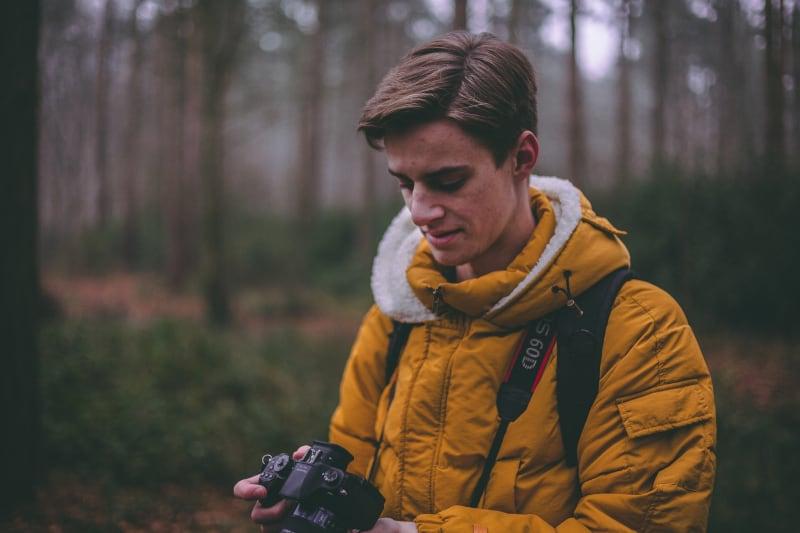 Mann stehend, der DSLR auf Wald hält