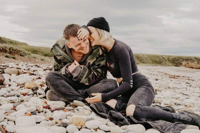 Mann und Frau lachen beim Sitzen auf Felsen