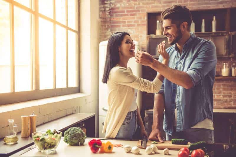 Schönes junges Paar füttert sich gegenseitig und lächelt beim Kochen in der Küche zu Hause