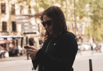 Mädchen in der Stadt Taste auf dem Handy