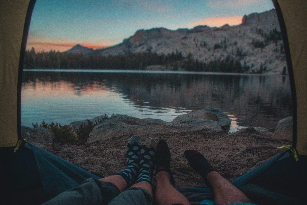 die Beine eines Mannes und einer Frau in einem Zelt an einem Bergsee