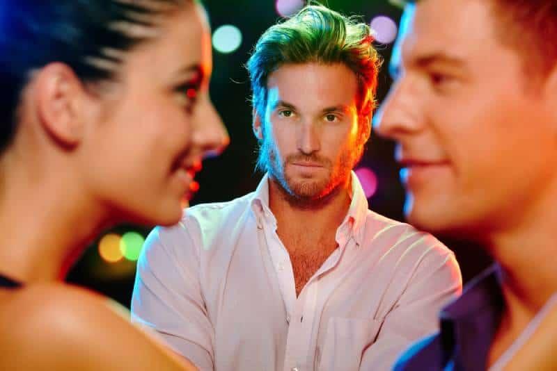 eifersüchtiger Mann, der Mann und Frau auf Tanzfläche betrachtet