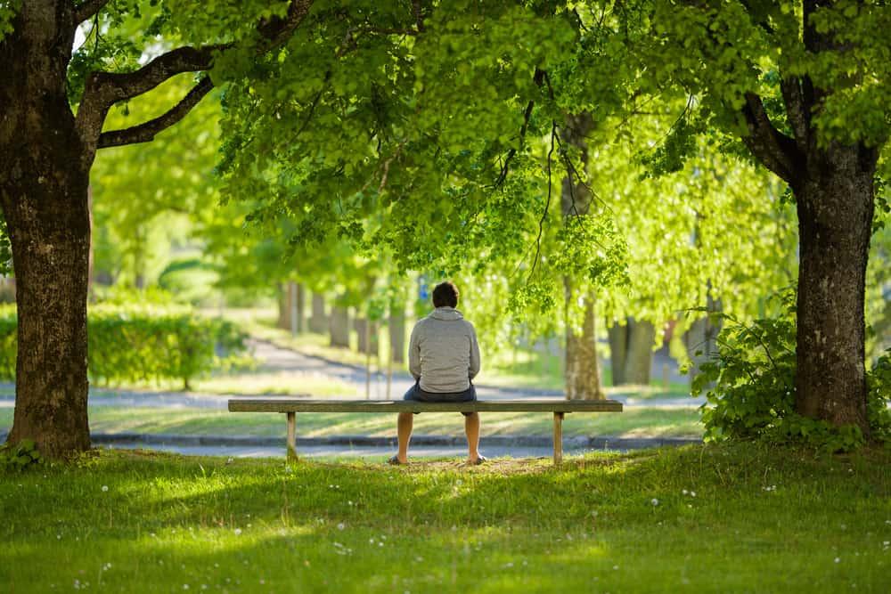 ein Mann, der alleine auf einer Parkbank sitzt