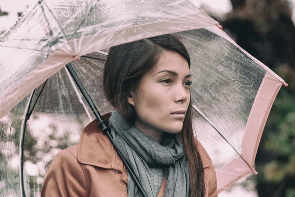 ein Porträt einer traurigen Brünette unter einem Regenschirm