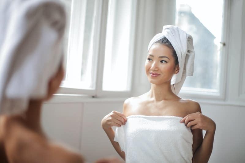 ein Spiegelbild im Spiegel einer lächelnden Frau nach dem Baden