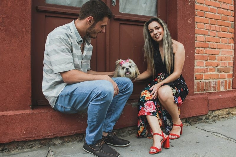 ein glückliches Liebespaar mit ihrem Haustier, das vor der Tür sitzt
