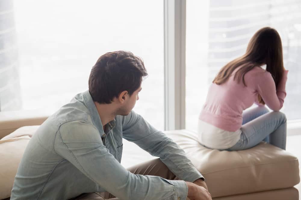 ein junges Paar sitzt nach einem Streit auf der Couch