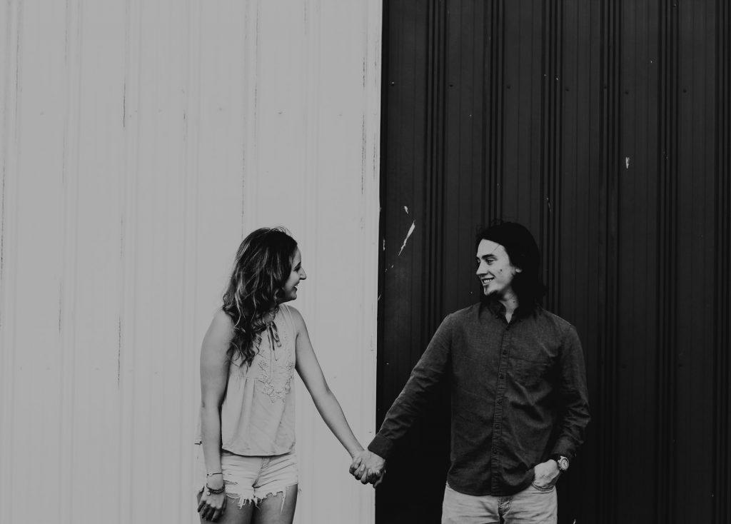 ein lächelndes Liebespaar Händchen haltend
