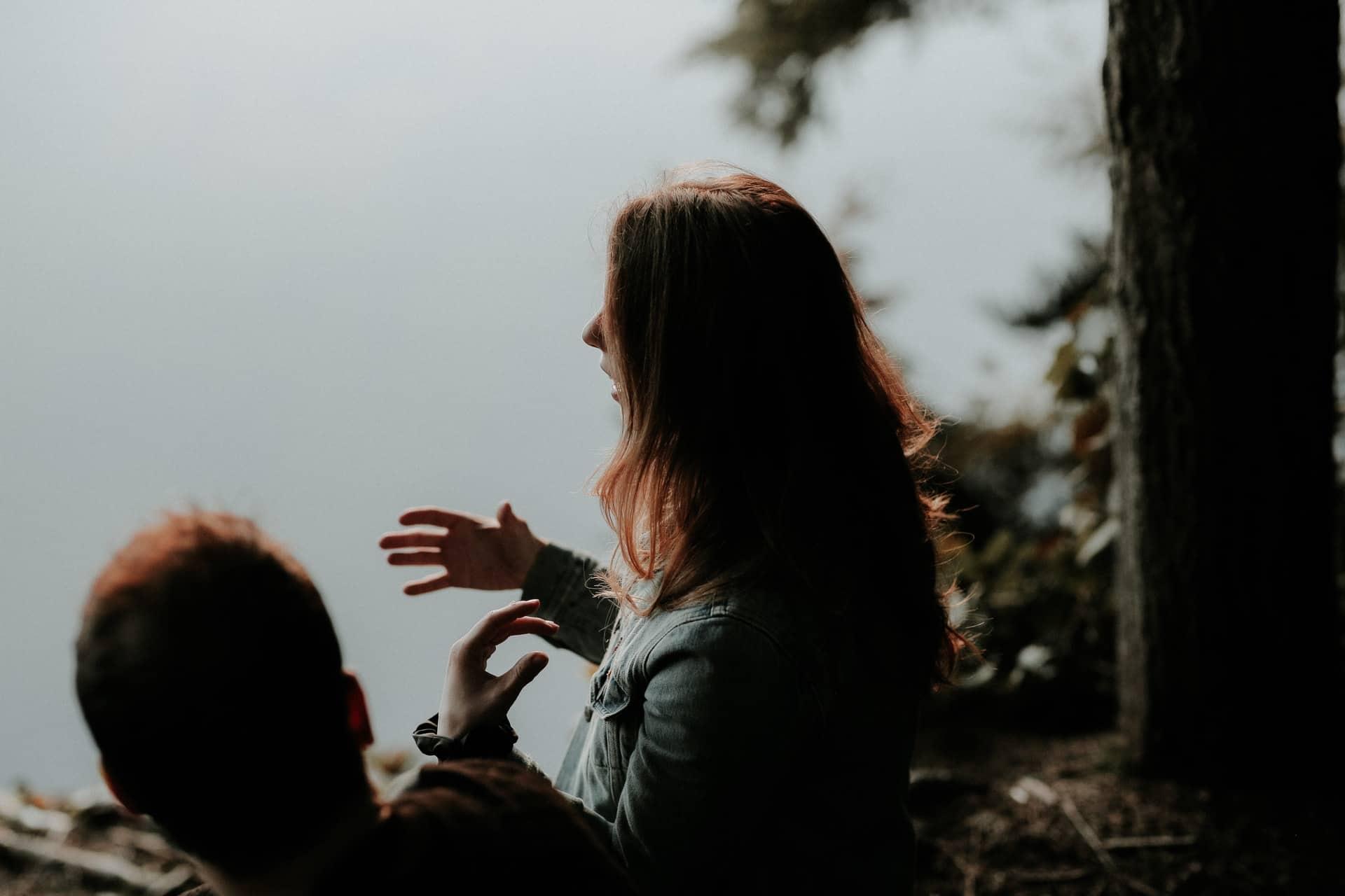 eine Frau, die mit ihrem Mann an einem Fluss unter einem Baum spricht