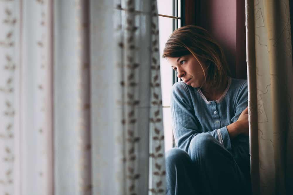 eine junge traurige Frau, die aus dem Fenster schaut