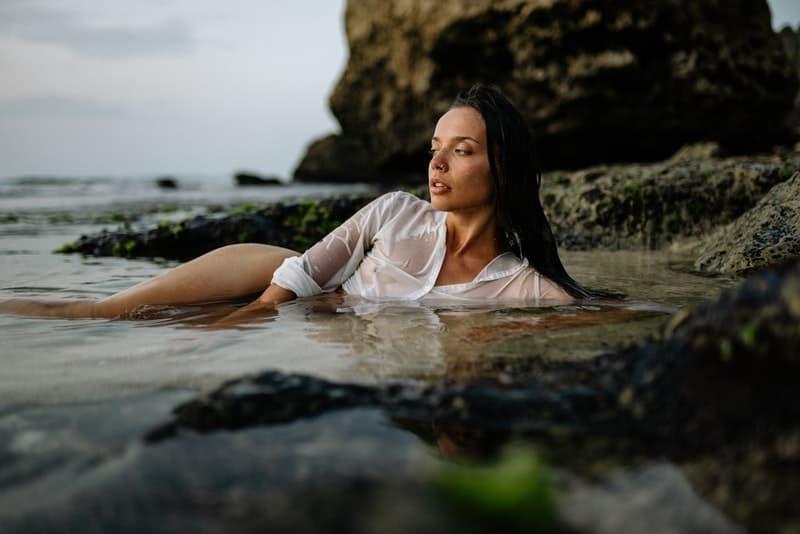 eine sexy Frau in einem weißen Hemd, die im Flachwasser des Meeres liegt