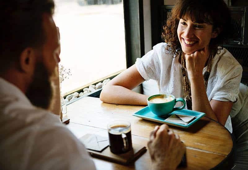 eine zufriedene Frau, die mit ihrem Mann Kaffee trinkt