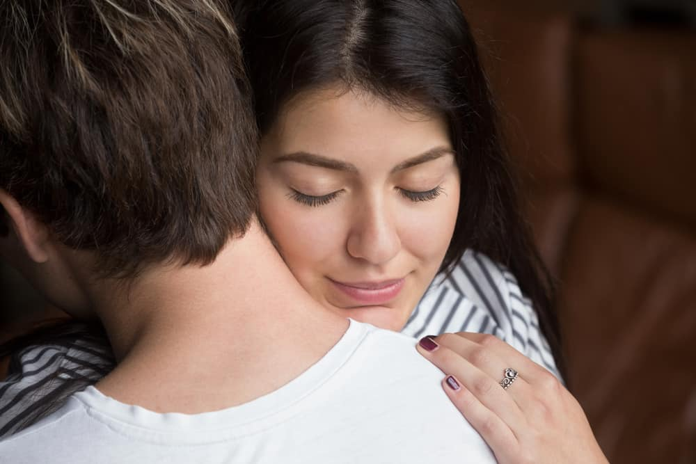 eine zufriedene Frau in der Umarmung ihres Mannes
