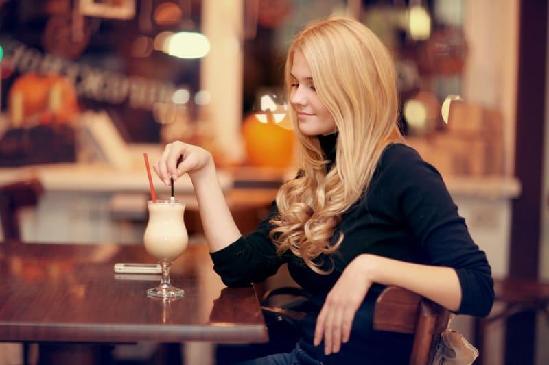 fröhliches Mädchen, das Kaffee trinkt