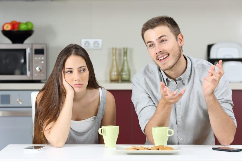 gelangweilte Frau hört ihrem Mann zu