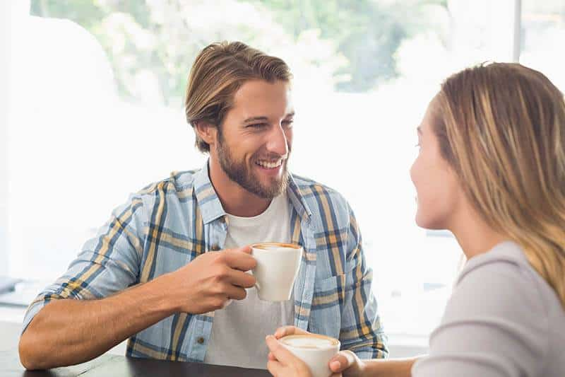 glückliches Paar spricht beim Kaffeetrinken